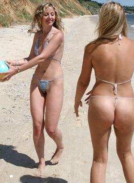 Beach girls in mini bikinis playing a ball in the water