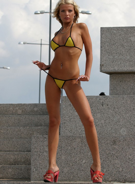 A girl in tight skirt showing a yellow string bikini with cameltoe outside