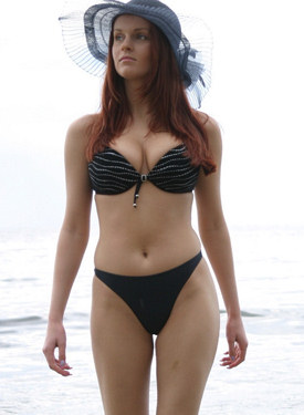 Busty hottie in black bikini and hat poses on the beach