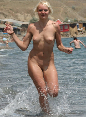 Young blonde with erected nipples running nude on the beach line and swimming in the water