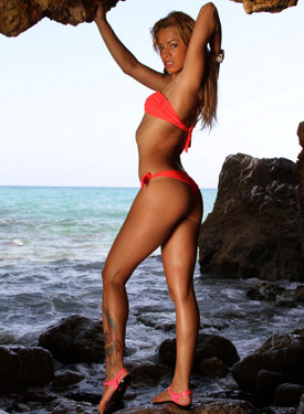 Perfect body blonde in red bikini strips in the see rock cave
