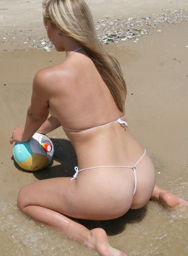 Exciting blonde goddess on the beach in white micro bikini