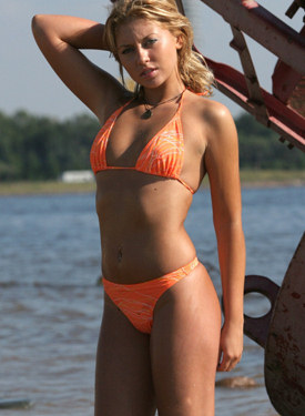 Beautiful sexy blonde in the sea and on the beach in orange bikini